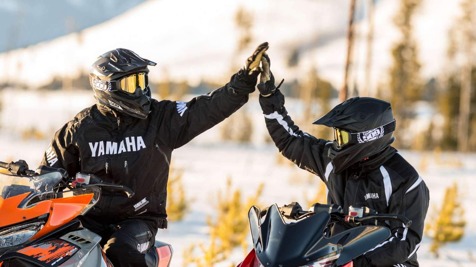 Yamaha Adventures snowmobilers doing a high five at Horseshoe Resort