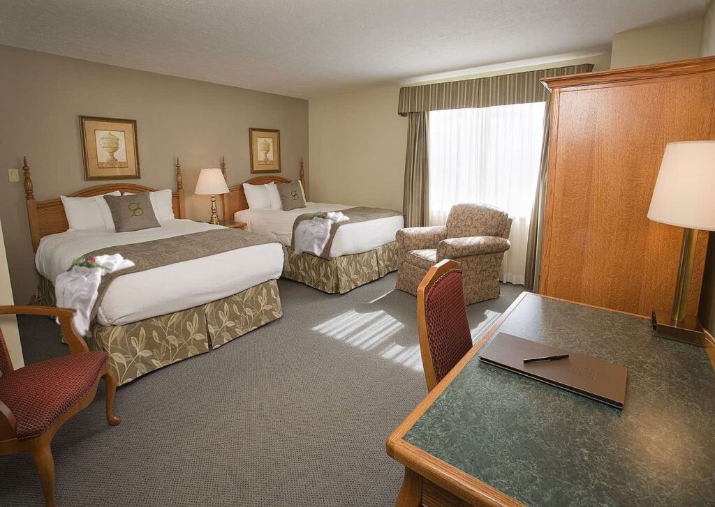 Stone Gate Inn is one of the best hotels in Orillia- bedroom with bathrobes and rose