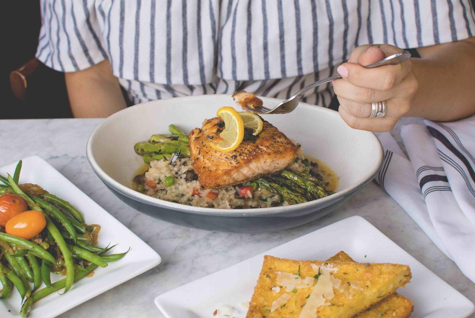 travis-yewell-restauranrs in Orillia woman eating fish-unsplash
